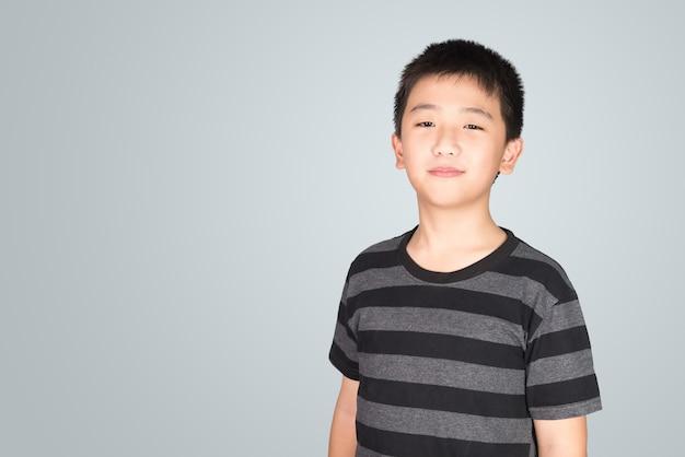 灰色の背景クリッピングパスに笑って幸せなアジアタイ少年のスタジオポートレート。