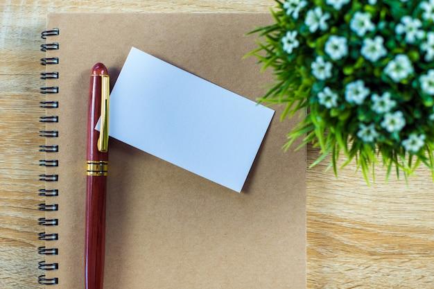 作業テーブルの上のノートオーガナイザーと空白の名刺または名刺