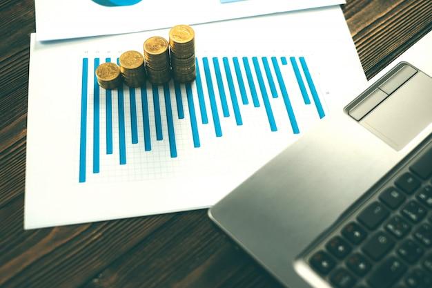 ノートパソコンと白い紙の上の財務グラフコインスタック