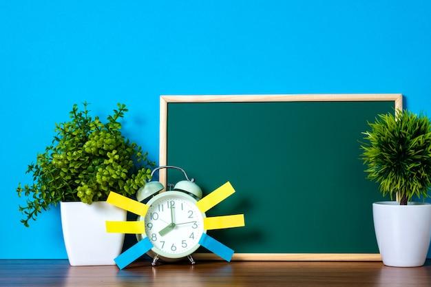 メモ用紙付箋とビンテージの目覚まし時計と空白の緑の黒板