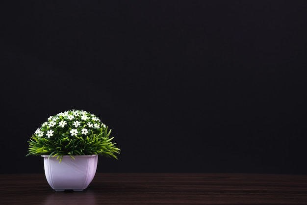 木製のテーブル暗い部屋に白い花瓶の小さな装飾的な木と花の花束。