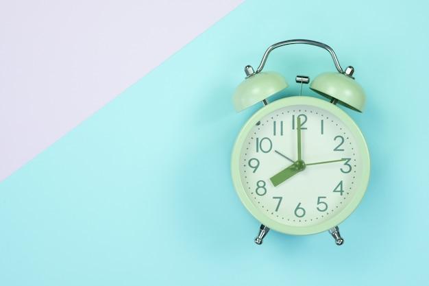 甘いパステルカラーの紙平面図、背景テクスチャ、ピンク、紫、黄色、ベージュ、緑、青の色のビンテージの目覚まし時計。