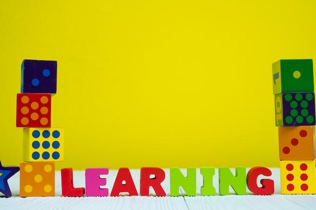 黄色の背景を持つテーブル上の学習テキストのアルファベットとおもちゃの正方形ブロックパズル