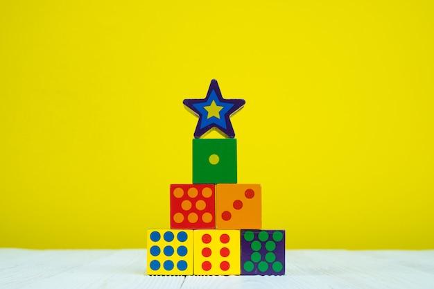 黄色の背景を持つテーブルの上の正方形ブロックパズルおもちゃ