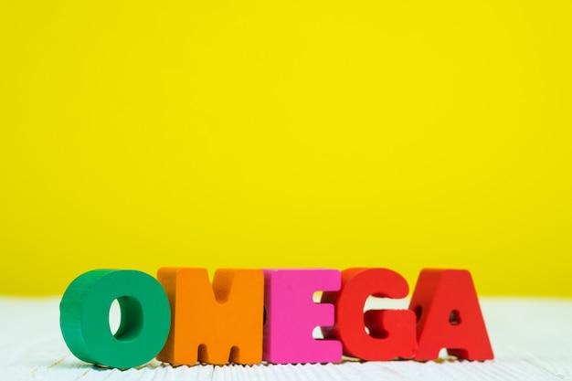 Омега текст алфавит на белом фоне деревянный стол желтый фон с копией пространства.