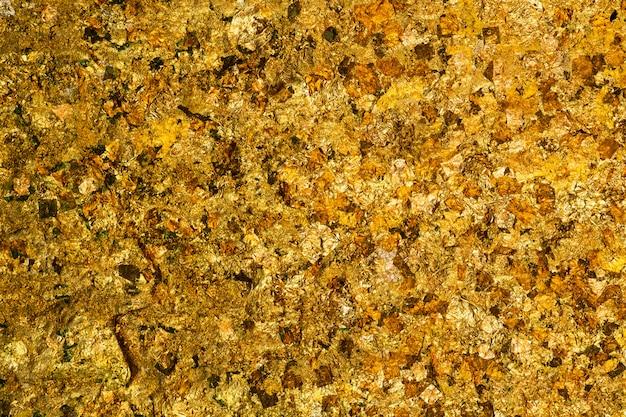 光沢のある黄色の金箔または金箔背景テクスチャのスクラップ