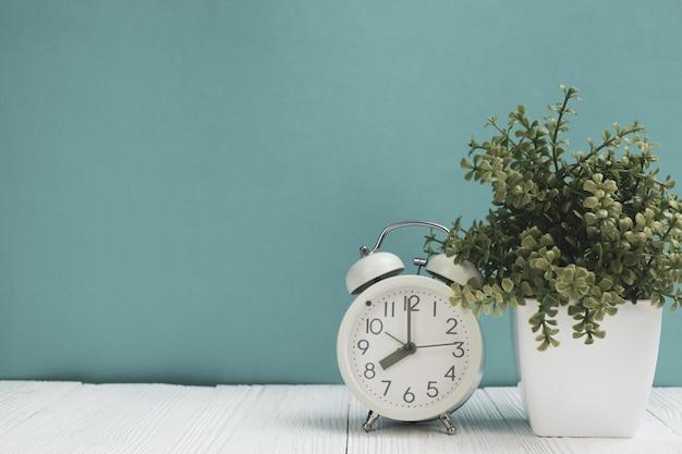 Маленькое декоративное дерево и букет цветов в белой вазе с винтажным будильником на деревянном столе с копией пространства