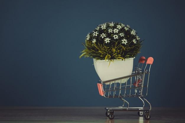 ビジネス金融のショッピングやマーケティングの概念のためのコピースペースを持つテーブルの上の小さなデコレーションツリーとショッピングカートやスーパーマーケットのトロリー。