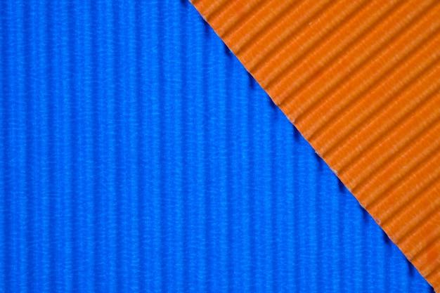 青とオレンジ色の段ボール紙のテクスチャ、背景に使用します。テキストやオブジェクトを追加するための空のスペースで鮮やかな色。