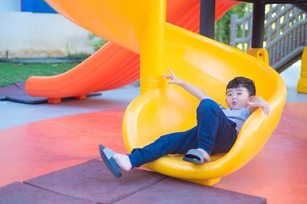 アジアの子供が夏の日差しの下で遊び場でスライドをプレイ