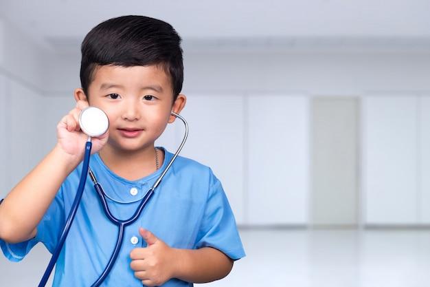 カメラ、健康的な概念を見て聴診器を保持している青い医療制服を着たアジアの子供の笑顔。