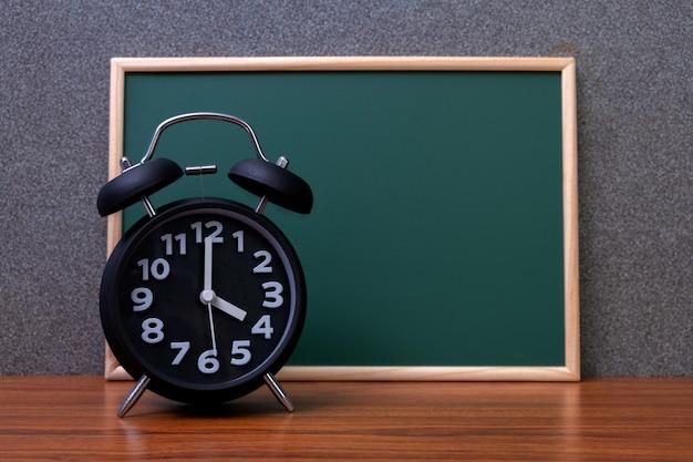 緑の黒板と黒のビンテージの目覚まし時計