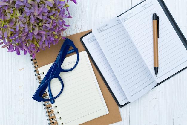 空白のノートブック紙とペンと事務用品、トップビューでグラス。
