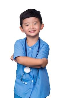 クリッピングパスを白で隔離される聴診器を保持している青い医療制服を着たアジアの子供の笑顔。