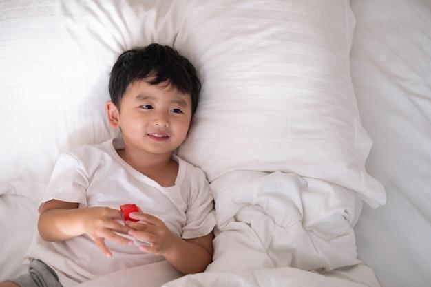 アジアの少年が自宅のベッドの上