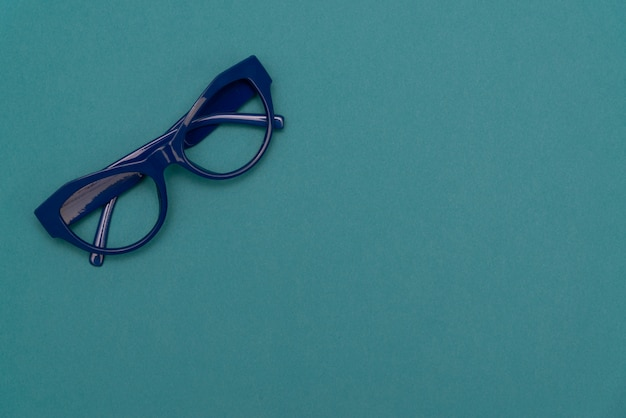 Плоский вид сверху, современные синие очки на пастельной бумаге