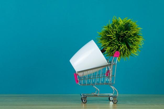 ショッピングカートやテーブルの上の小さなデコレーションツリーとスーパーマーケットのトロリー