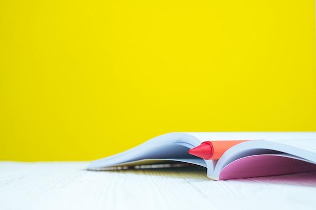 黄色の背景を持つ本とワックスクレヨン鉛筆の山。