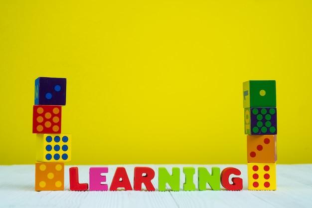 黄色の背景を持つ学習テキストアルファベットとおもちゃの正方形ブロックパズル