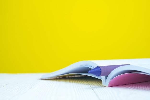 黄色の背景を持つ本とカラフルのワックスクレヨン鉛筆の山。