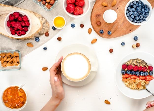 Здоровый завтрак фон с овсяной кофе, ягоды, яйца, орехи, вид сверху