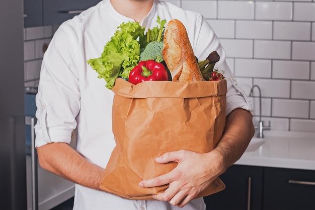 さまざまな野菜や他の製品の紙袋を持って男