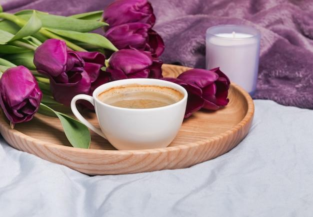 一杯のコーヒー、チューリップ、キャンドルのクローズアップ