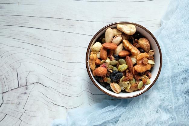 白いテーブルの上にミックスナッツをボウルします。