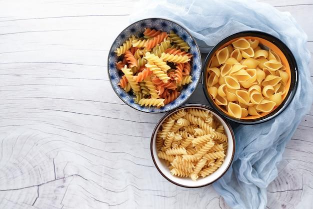 Разнообразие видов и форм сухой итальянской пасты в миске.