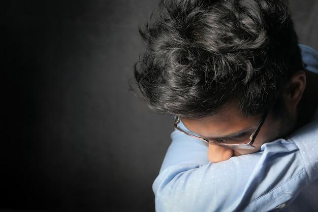 Молодой больной человек, охватывающий ее нос и рот рукой.