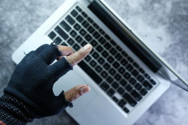夜にラップトップからデータを盗むハッカーの手