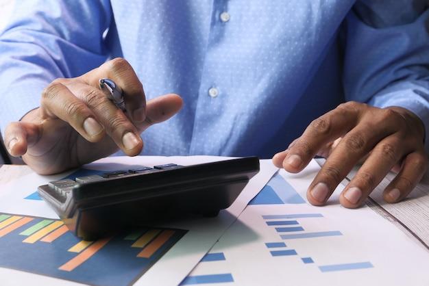 Рука бизнесмена используя калькулятор на столе офиса