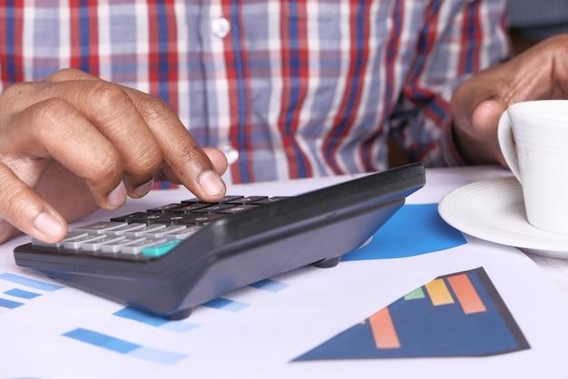 Человек рука с помощью калькулятора на рабочий стол.