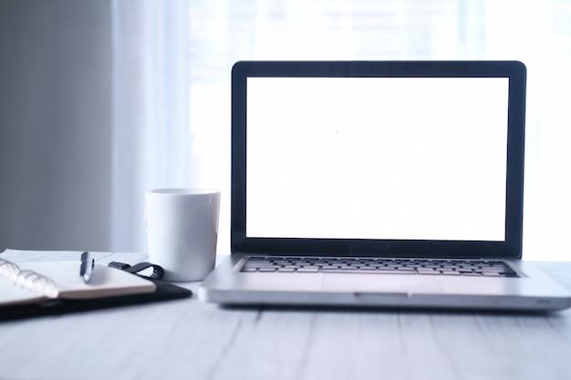 Компьтер-книжка с пустым экраном с кружкой белого кофе на столе офиса.
