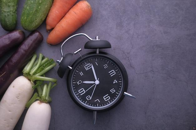 健康的なフィットネスと時計と野菜のテーブルの上の果物のコンセプト。