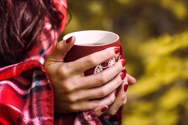 Чашка травяного чая в руках женщины. осенняя осень крупным планом, сезонный напиток на открытом воздухе в лесу.