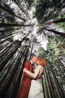 若い結婚式の流行に敏感なカップルの新郎と新婦が夏の日に緑の森でハグとキスをします。