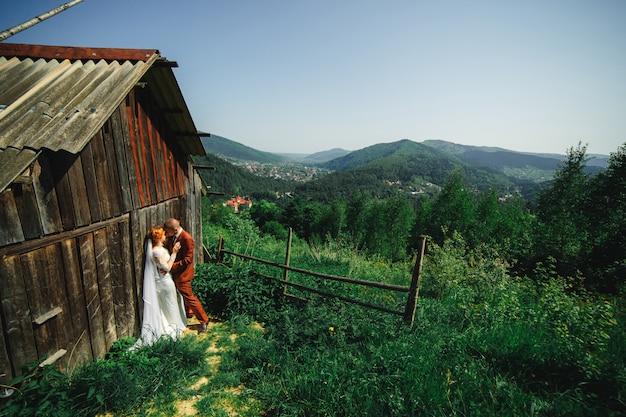 山での結婚式のカップル。新郎と新婦が素朴な家の近くで抱いています。カップルの背後にある山々の美しい景色