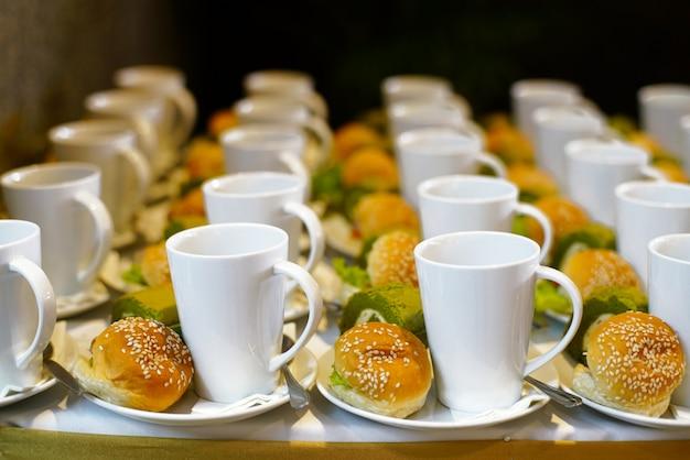 ベーカリーと飲み物の白いカップとコーヒーブレーク時間やパーティーでの食事のための皿