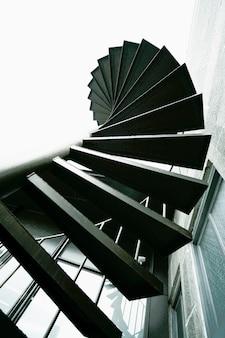 白い空に木目調とノイズの質感を備えた黒い金属製の外部螺旋階段、上昇角度ビュー、成功と目標のマイルストーンへのステップアップ。