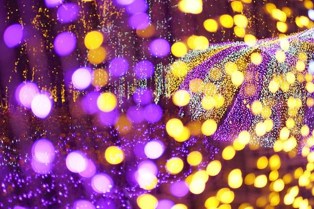 イルミネーションされた紫色と金色のボケ円形の光拡散背景