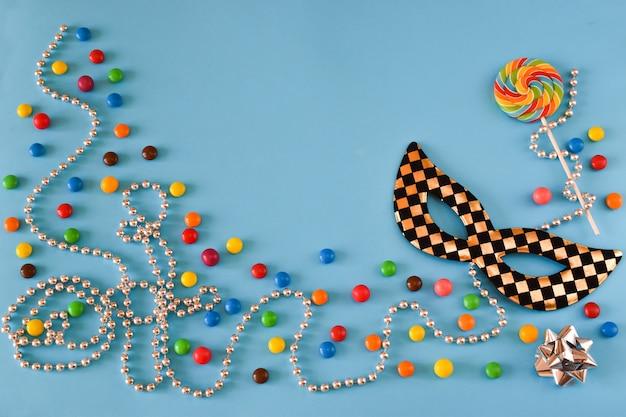 下部にある色付きのキャンディー、ビーズ、マスク。カーニバルのテキストのお祭りの背景。フラットなレイアウト。