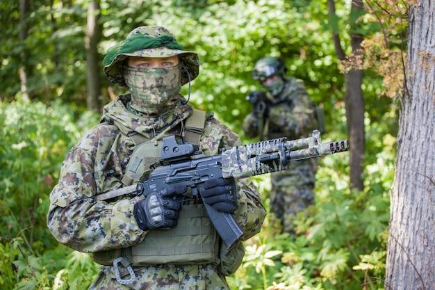 Военный в камуфляже с оружием в лесу