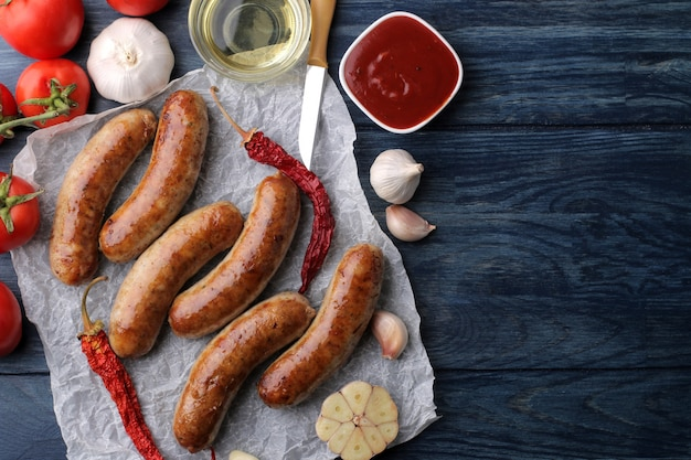 Вкусные колбаски гриль на бумаге с красным соусом и специями на синем фоне деревянных