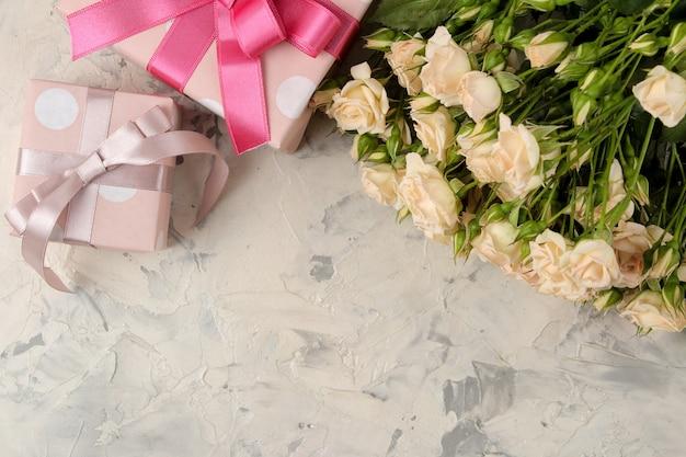 美しい柔らかいミニバラの花束と明るいコンクリート背景のギフトボックス