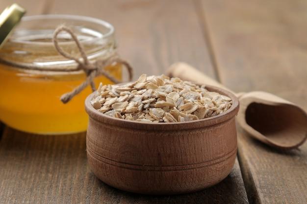 Сухая овсянка в деревянной миске и мед на коричневом деревянном столе