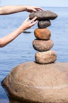 水の近くの大きな丸い石のスタックを作る人間の手