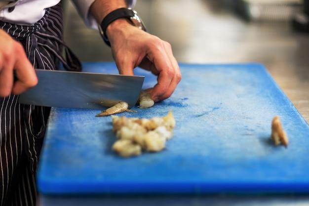 Шеф-повар режет сырые креветки