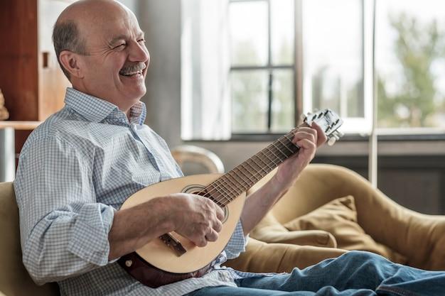 Пожилой мужчина учится играть на гитаре