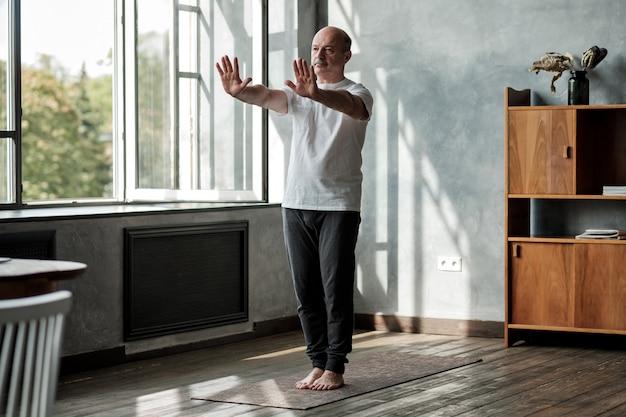 Пожилой мужчина делает упражнения в домашних условиях